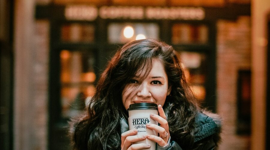 Girl with coffee in front of lighted coffee sign - coffee affects on skin