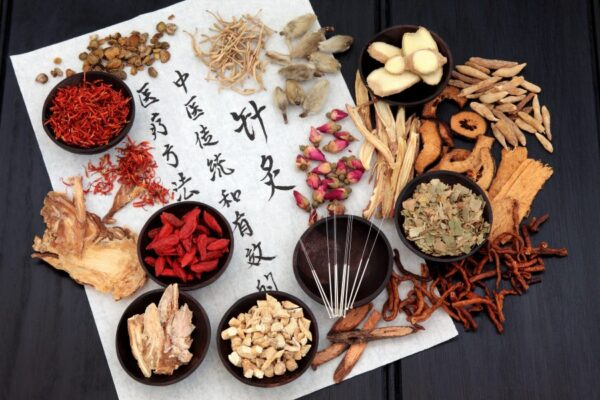 Herbs in small bowls on scroll with Chinese script - oriental medicine dermatology
